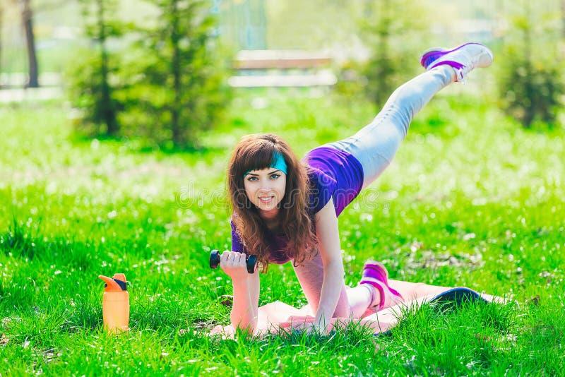 Menina da aptidão no parque e contratada em vários exercícios com peso e esteira a morena vai dentro para esportes fora imagem de stock