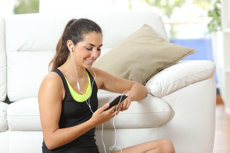Menina da aptidão que escuta a música com fones de ouvido foto de stock