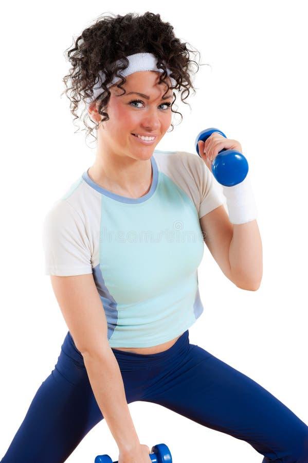 Menina da aptidão que exercita com os pesos, sorrindo fotografia de stock royalty free