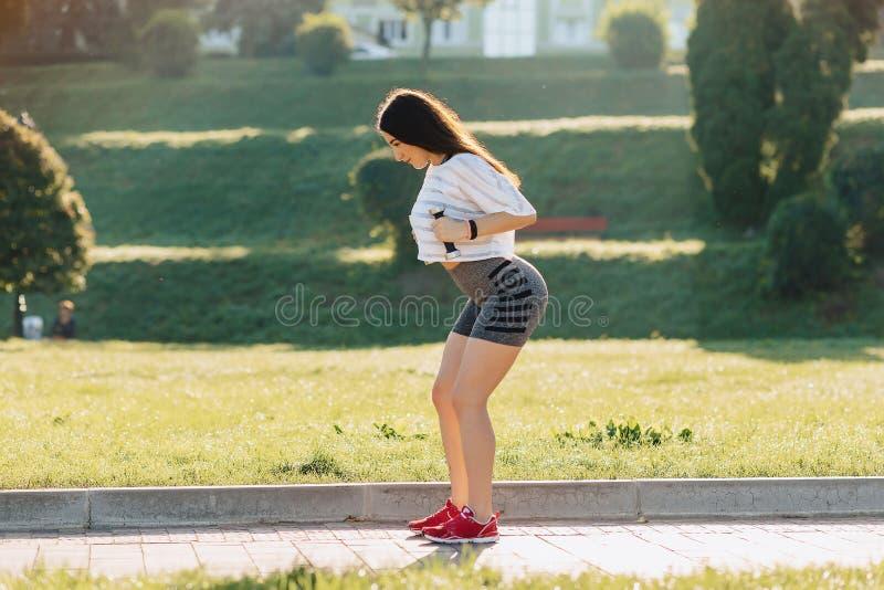 menina da aptidão que faz exercícios com pesos no por do sol na grama fotografia de stock royalty free
