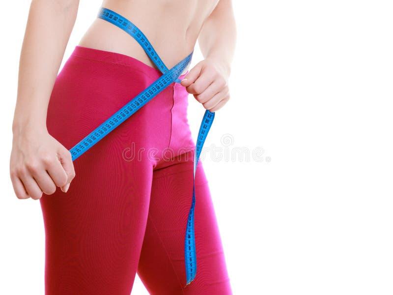 Menina da aptidão que mede sua cintura isolada. Perda de peso. imagens de stock