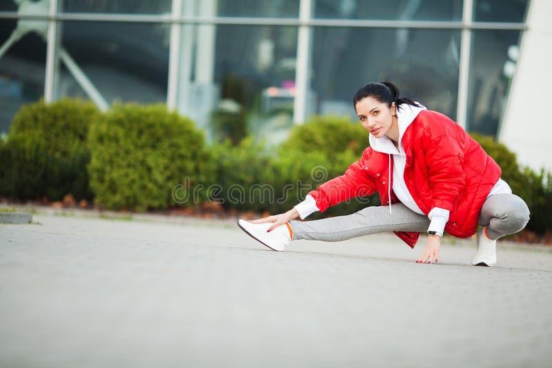Menina da aptid?o Mulher nova dos esportes que estica na cidade moderna Estilo de vida saud?vel na cidade grande imagens de stock