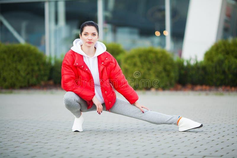 Menina da aptid?o Mulher nova dos esportes que estica na cidade moderna Estilo de vida saud?vel na cidade grande foto de stock royalty free
