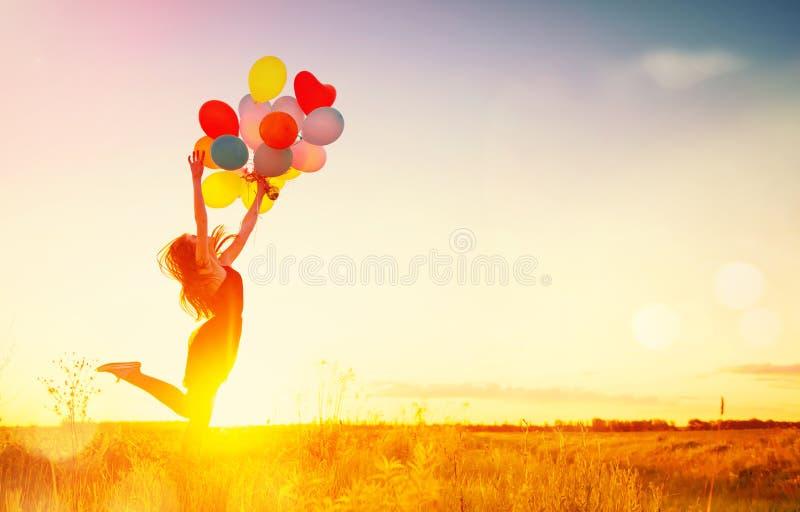 Menina da beleza com os balões de ar coloridos sobre o céu do por do sol imagens de stock