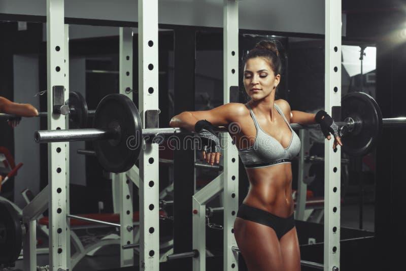 Menina da beleza com os pesos que descansam no gym imagem de stock
