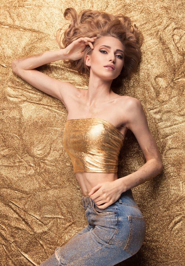 Menina da beleza da forma que encontra-se no brilho dourado foto de stock royalty free