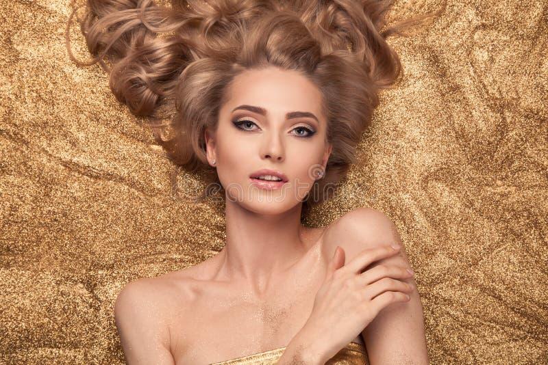 Menina da beleza da forma que encontra-se no brilho dourado foto de stock