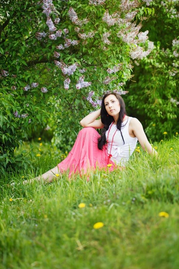 Menina da beleza de mola. Jovem mulher bonita que senta-se no verde fotos de stock royalty free