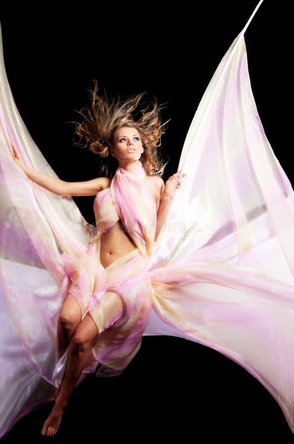 Menina da beleza no balanço com matéria têxtil da cor fotografia de stock royalty free