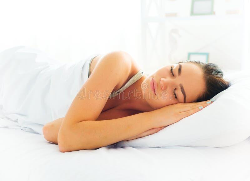 Menina da beleza que dorme em sua cama confortável foto de stock