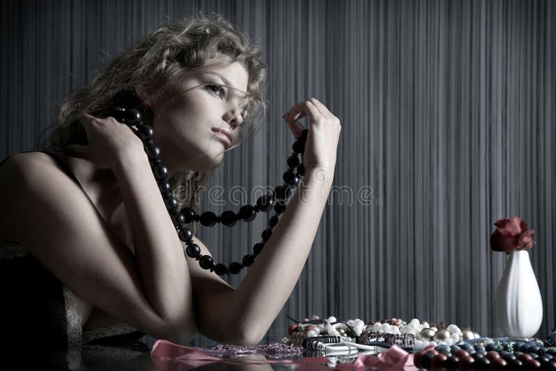 A menina da beleza senta-se na tabela com acessórios imagem de stock