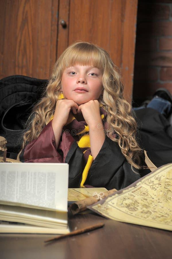 Menina da bruxa com livro da pilha imagens de stock