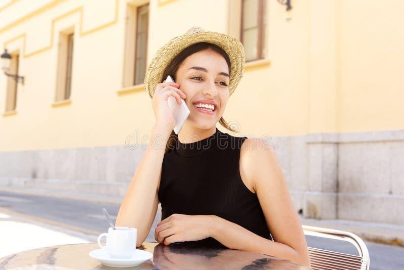 Menina da cidade que fala no telefone celular no café exterior fotografia de stock