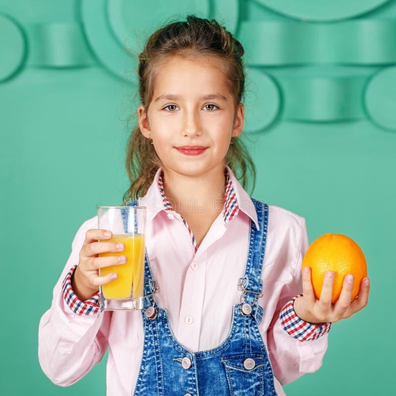 A menina da criança bebe o suco de laranja para o quadrado do café da manhã O conceito fotos de stock royalty free