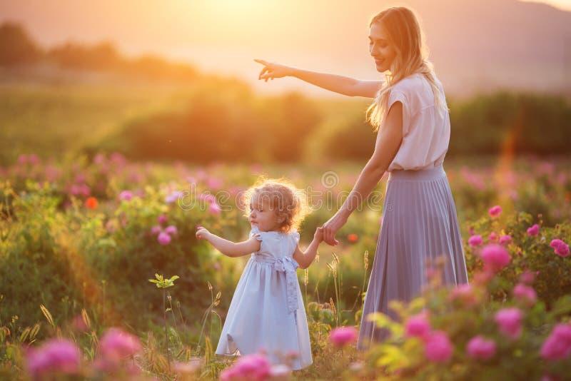 A menina da criança bonita com a mãe feliz nova está vestindo a roupa ocasional que anda no jardim de rosas sobre luzes do por do imagem de stock royalty free