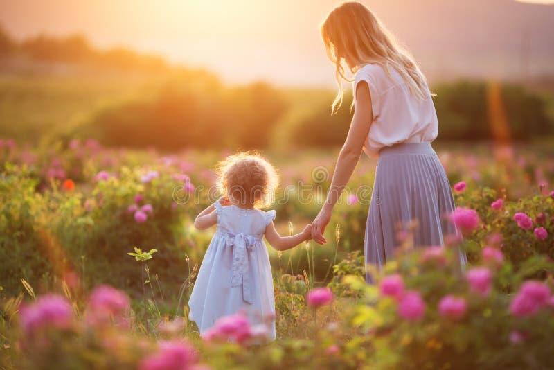 A menina da criança bonita com a mãe feliz nova está vestindo a roupa ocasional que anda no jardim de rosas sobre luzes do por do fotografia de stock royalty free