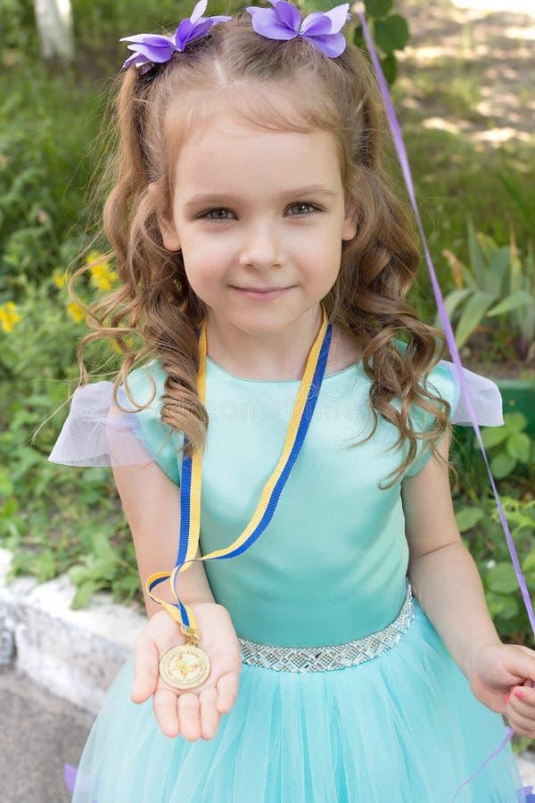 Menina da criança bonita com medalha de ouro imagens de stock royalty free