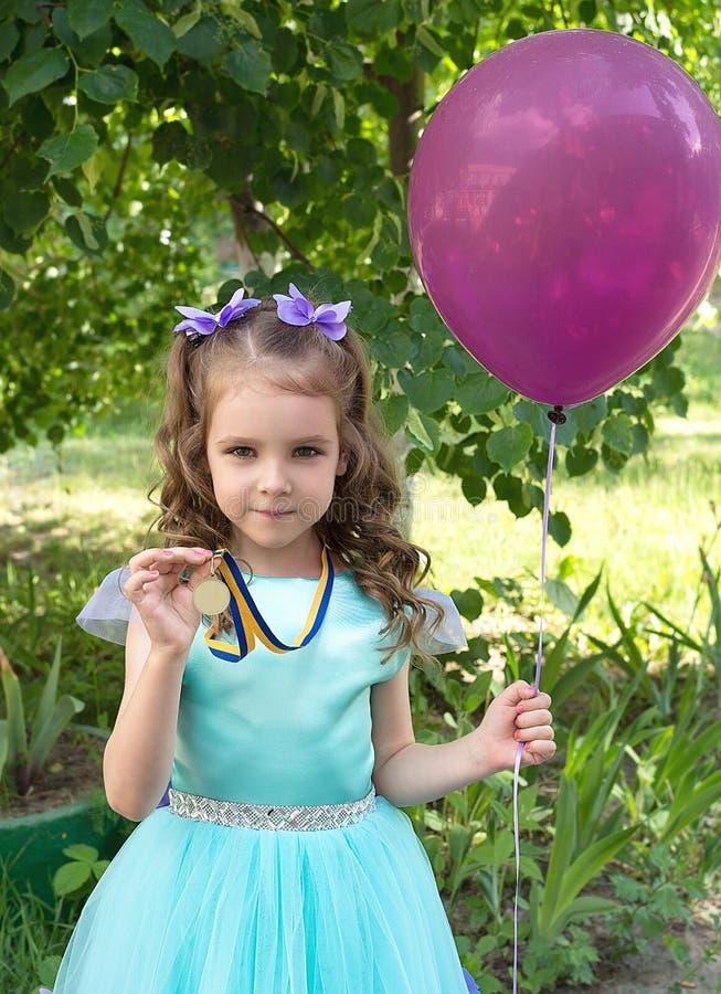 Menina da criança bonita no vestido elegante com ballon da medalha e do ar de ouro imagens de stock royalty free
