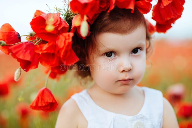 Menina da criança com o ramalhete das papoilas foto de stock royalty free