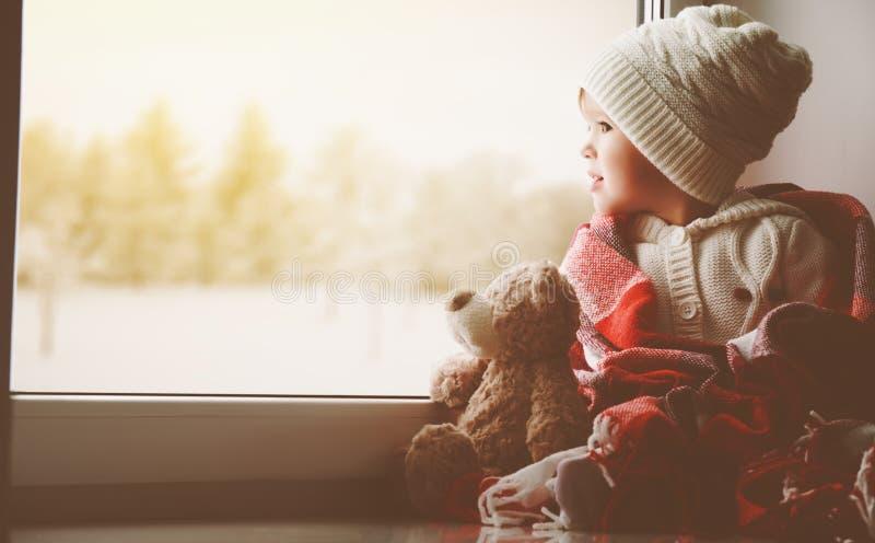 Menina da criança com o urso de peluche na janela e a vista do wint imagens de stock
