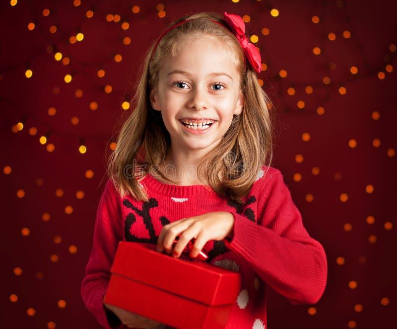 Menina da criança com presente de Natal na obscuridade - vermelho com luzes imagem de stock
