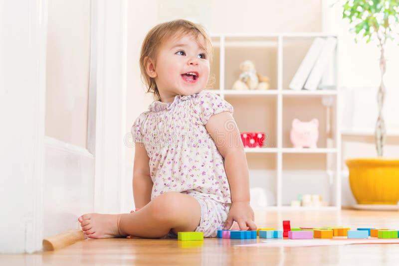 Menina da criança com um sorriso grande que joga com blocos de madeira do brinquedo foto de stock