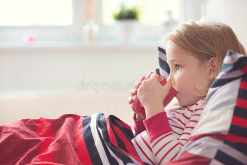 Menina da criança consideravelmente pequena que coloca no chá da cama e da bebida fotografia de stock royalty free
