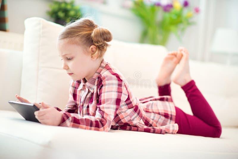 Menina da criança consideravelmente pequena que usa uma tabuleta digital imagens de stock