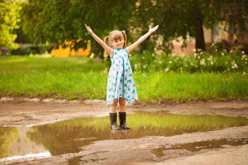 A menina da criança corre através de uma poça ver?o exterior fotografia de stock royalty free