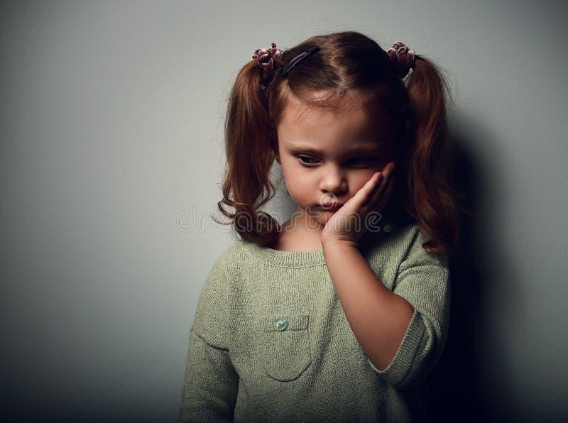 Menina da criança da tristeza que olha infeliz Retrato do close up na obscuridade imagem de stock royalty free