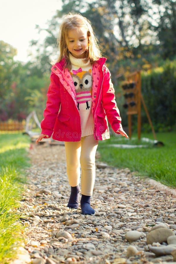 Menina da criança de 4 anos que anda sobre seixos imagens de stock
