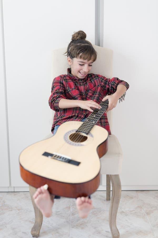 Menina da criança de 10 anos que joga a guitarra espanhola foto de stock royalty free
