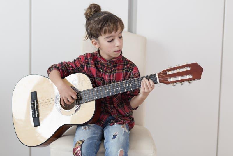 Menina da criança de 10 anos que joga a guitarra espanhola fotos de stock royalty free