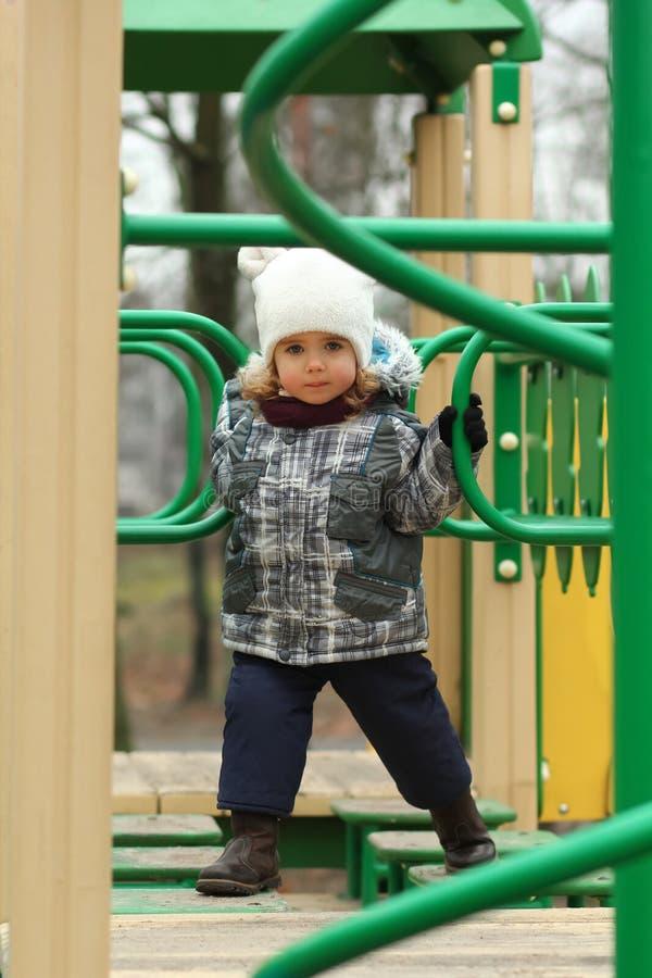 Menina da criança de dois anos que supera o curso de obstáculo no campo de jogos imagens de stock royalty free