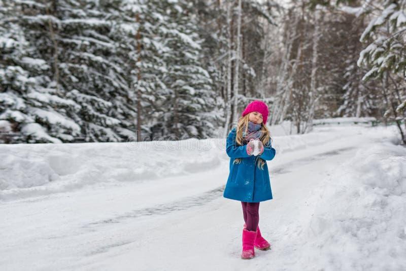 Menina da criança de seis anos em um revestimento azul e em um chapéu cor-de-rosa e botas que fazem caretas na floresta do invern foto de stock royalty free
