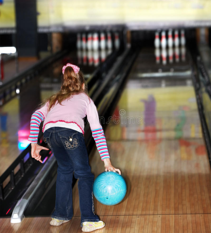 Menina da criança dentro com esfera de bowling. imagem de stock