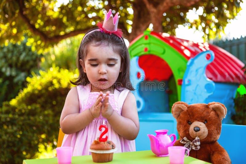 Menina da criança do bebê nas mãos de aplauso da segunda festa de anos exterior no bolo com Teddy Bear como o melhor amigo fotos de stock