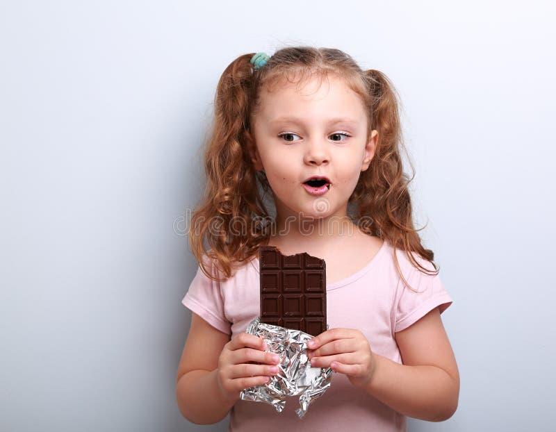 Menina da criança do divertimento que come o chocolate escuro e que surpreende como ele saboroso fotografia de stock