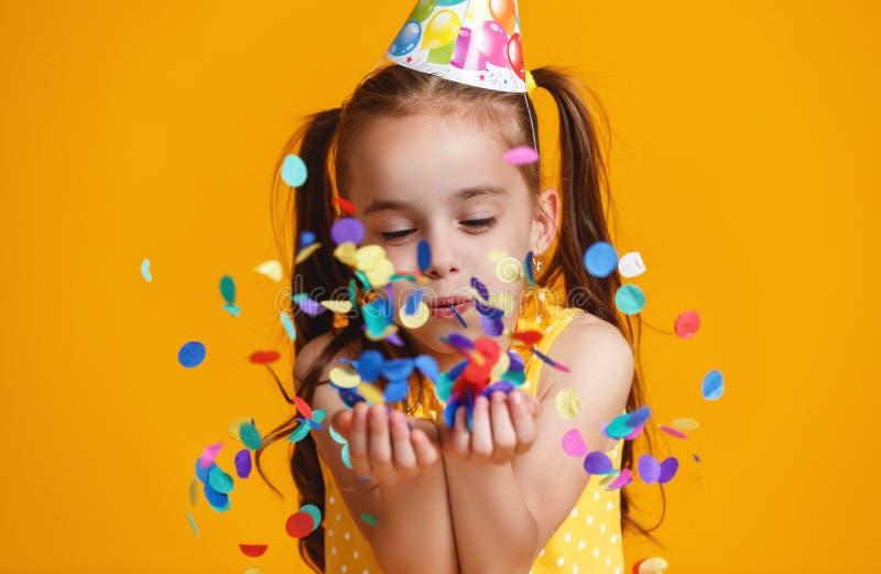 Menina da criança do feliz aniversario com confetes no fundo amarelo fotos de stock