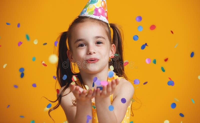 Menina da criança do feliz aniversario com confetes no fundo amarelo fotografia de stock royalty free
