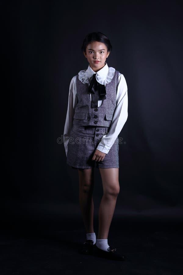 Menina da criança do negócio no suporte formal do terno no backgrou abstrato escuro foto de stock royalty free