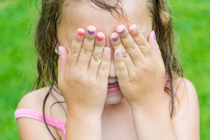A menina da criança don o ` t vê, cobrindo seus olhos e cara pelas mãos foto de stock