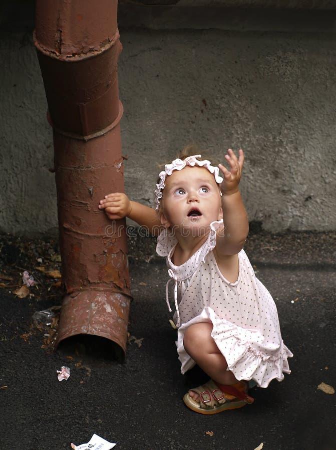 Menina da criança e tubulação da água da chuva imagens de stock