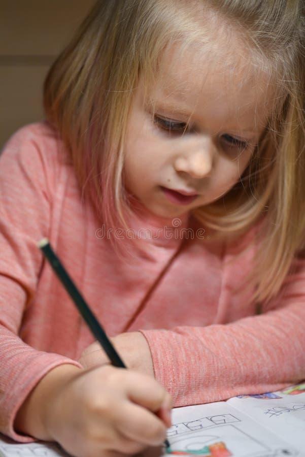 A menina da criança em idade pré-escolar da criança aprende selecionar em casa e escrever nos cadernos na noite sob a luz de uma  fotos de stock