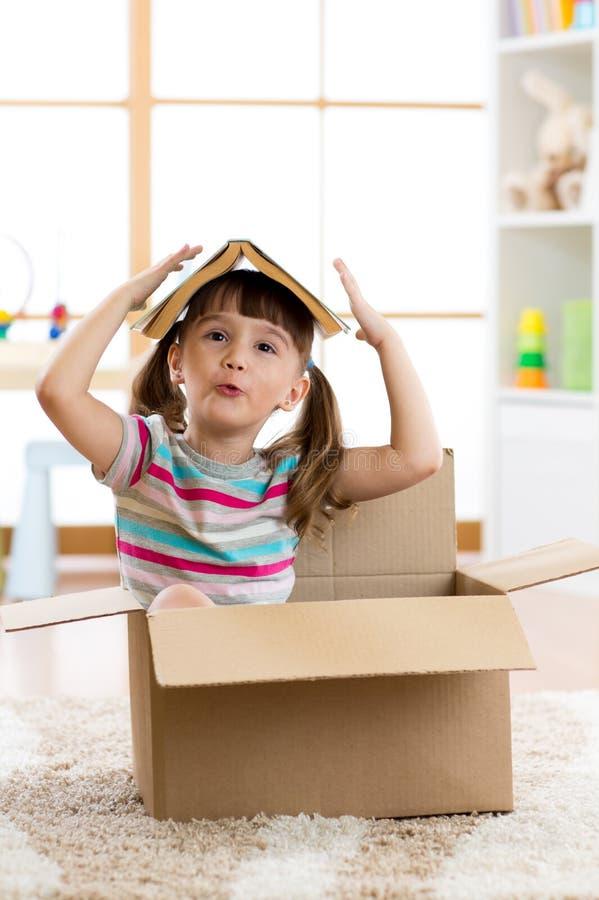 Menina da criança em idade pré-escolar da criança que joga em uma casa do brinquedo na sala do berçário foto de stock royalty free