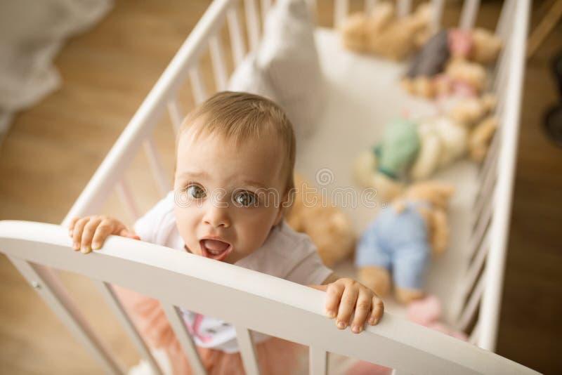 A menina da criança está na ucha entre os brinquedos imagens de stock