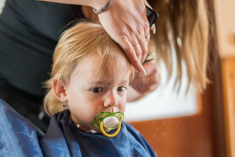 A menina da criança está obtendo-lhe o primeiro corte de cabelo fotos de stock
