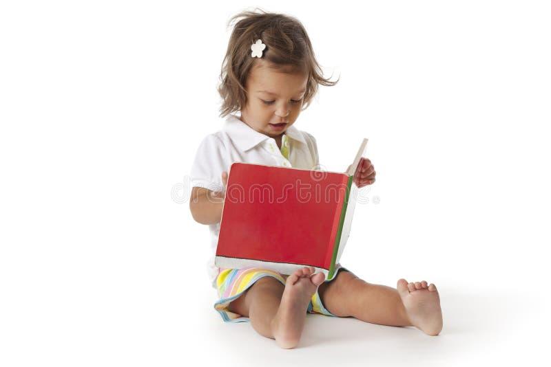 A menina da criança finge ler um livro imagem de stock