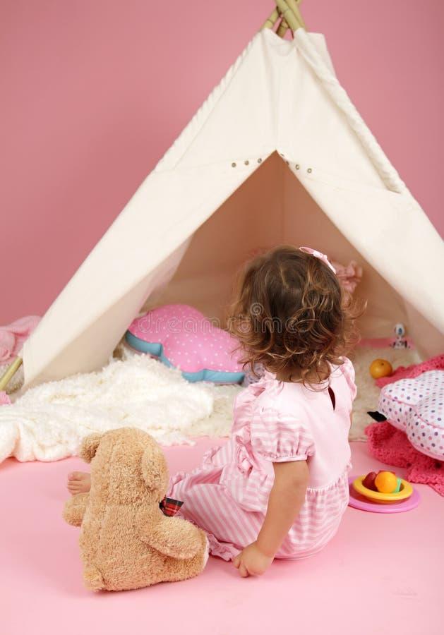 A menina da criança finge o jogo com barraca da tenda e o brinquedo enchido do urso foto de stock