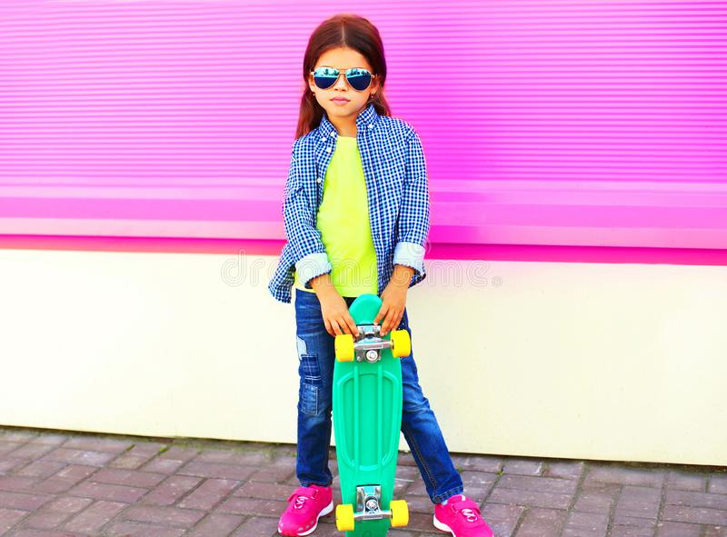 A menina da criança da forma guarda o skate na parede cor-de-rosa imagens de stock
